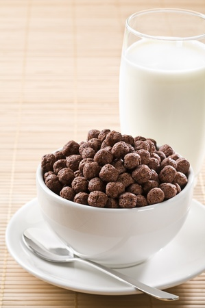 Milk with chocolate cereal balls close up photo