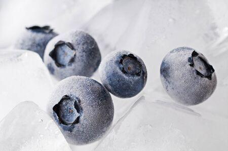 Frozen blueberries on ice background macro shoot photo