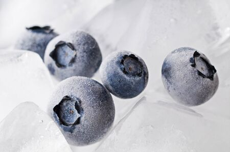 Frozen blueberries on ice background macro shoot