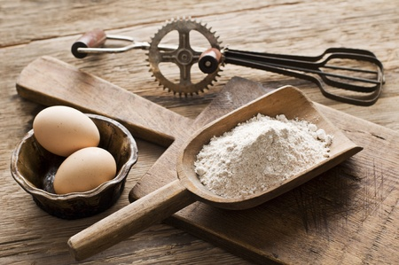pastries: Flour and eggs on wooden background - vintage Stock Photo
