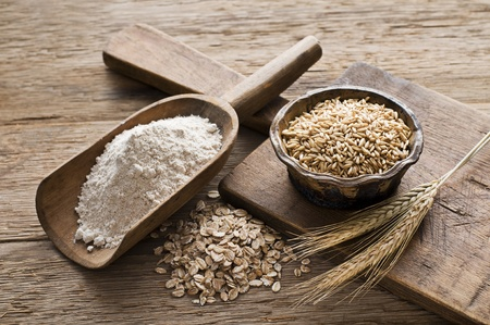 wheat grain: Whole grain and flour on wooden background close up