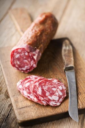 Fresh pork salami on wooden background close up