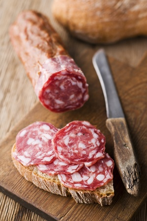 Fresh beef salami on wooden background close up