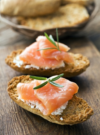Fresh salmon snack with curd and rosemary close up