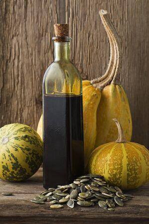 pumpkin seed: Fresh pumpkin oil on wooden background close up