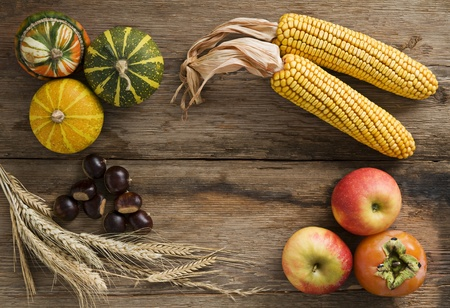 Pumpkins, corn, chestnuts, apple and persimmon fruit on wooden background photo