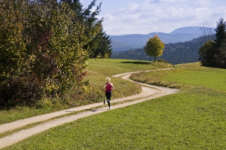 Young woman running outdoor in autumn time photo