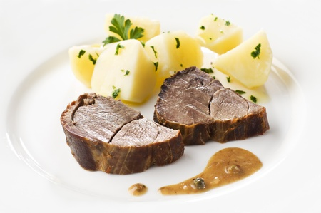 Roasted deer meat with boiled potatoes close up