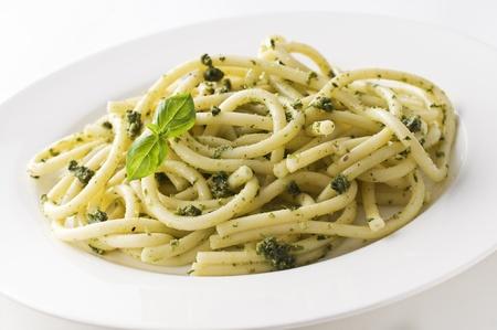 Fresh spaghetti pasta with basil pesto close up