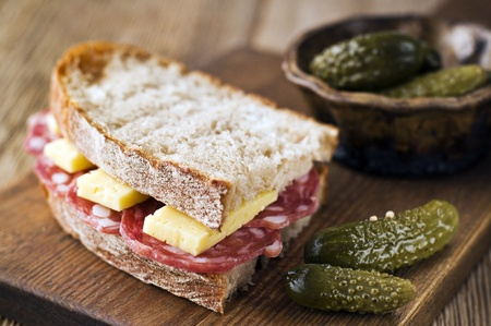 Fresh salami sandwich with cheese and gherkin close up