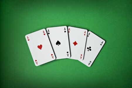 Poker aces on green background close up photo