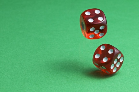 midair: Red dices in midair on green background close up Stock Photo