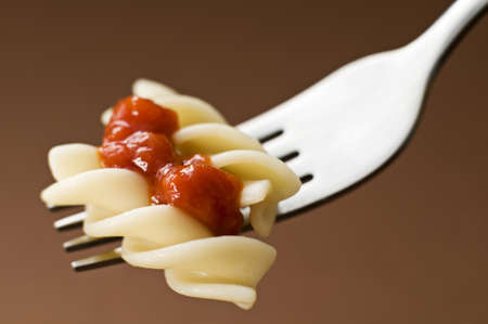 Fresh pasta with tomato sauce on fork close up Stock Photo - 12014474