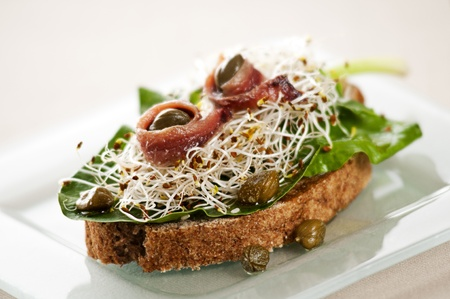 anchovy fish: Fresh sandwich with anchovies, capers, sprouts and salad