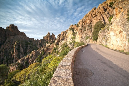 Road going through red cliffs in Corsica photo