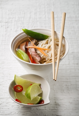 Chinese soup with beef, vegetables and noodles photo