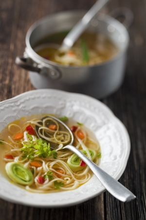 Chicken or beef soup with noodles close up photo