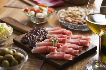 frankfurters: Full table of prosciutto, olives, cheese, salad and wine Stock Photo