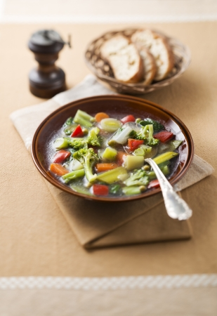 Vegetable soup in brown plate close up photo