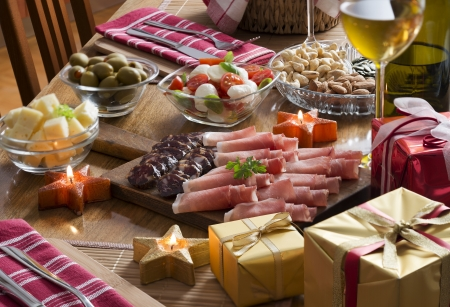 prosciutto: Full table of prosciutto, olives, cheese, salad and wine for holidays Stock Photo