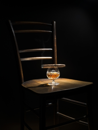 Cognac and cigar on wooden chair close up photo