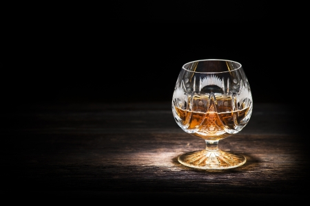 drunks: Cognac in crystal glass on wooden background