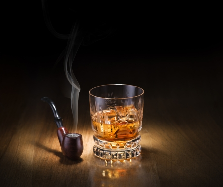 drunks: Whiskey and smoking pipe on wooden background