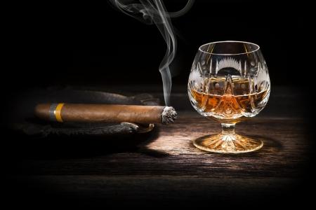 Coñac y cigarro en el fondo de madera de cerca
