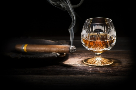 whiskey glass: Cognac and cigar on wooden background close up