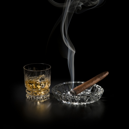 drunks: Whiskey and smoking cigar on black background close up Stock Photo