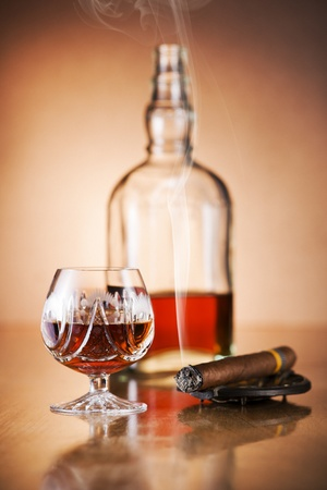 Cognac and cigar on wooden background close up photo