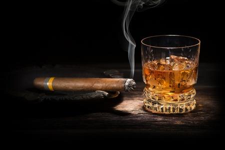 Whisky y cigarro en el fondo de madera de cerca Foto de archivo