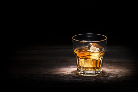Glass of whiskey on wooden background close up photo