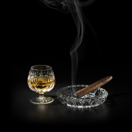 drunks: Cognac and smoking cigar on black background
