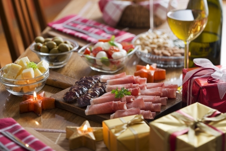 mediterranean cuisine: Full table of prosciutto, olives, cheese, salad and wine for holidays Stock Photo
