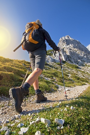 Young woman on a sunny day hiking in high mountains Stock Photo