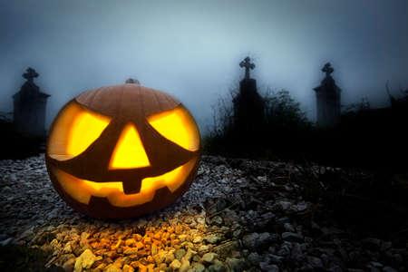 jack o lantern: A glowing Jack O Lantern in a dark mist graveyard on Halloween