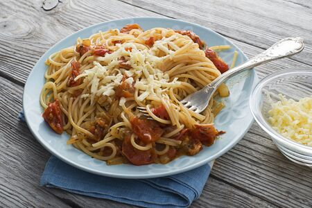 Spaghetti with tomato sauce and cheese close up photo