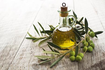 aceite de oliva: El aceite de oliva y la rama de olivo en la mesa de madera Foto de archivo