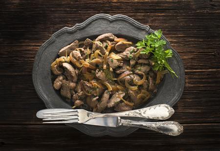 higado de pollo: Hígados de conejo con cebolla en el fondo de madera