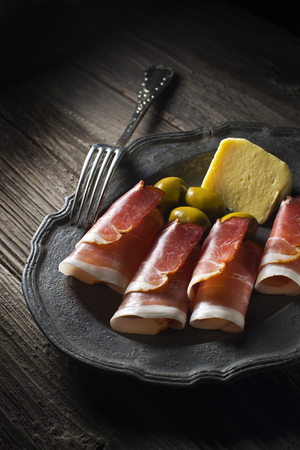 Prosciutto with olives and cheese close up photo