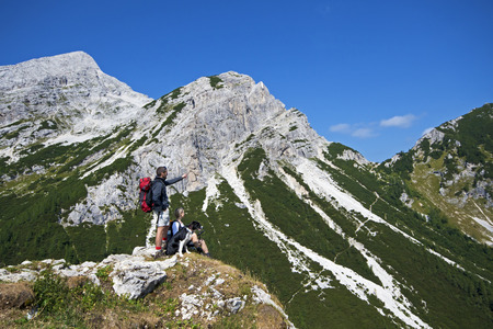 Hikers with backpacks enjoying view from top of a mountain photo