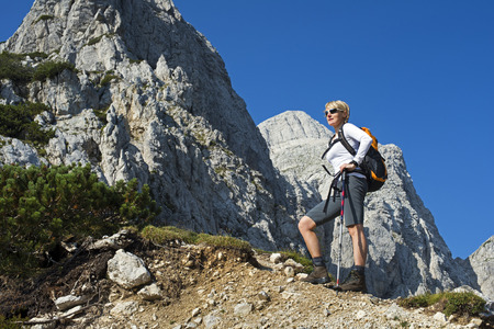 woman hiking: woman hiking in mountains on a sunny day Stock Photo