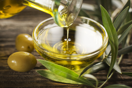 cooking oil: Bottle pouring virgin olive oil in a bowl close up Stock Photo