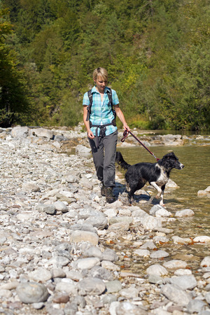 mountain dog: Young woman with dog hiking near River Stock Photo