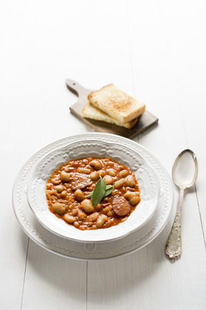 White bean stew with bread close up photo