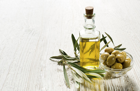 Olive oil and olive branch on the wooden table photo