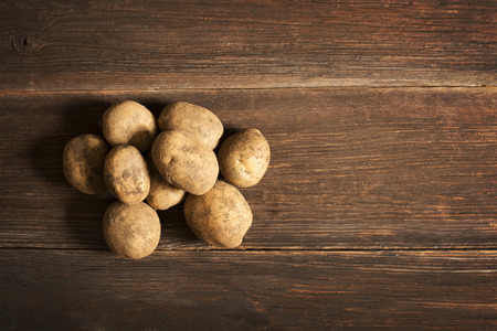 Bunch of potatoes on wooden background close up shoot photo