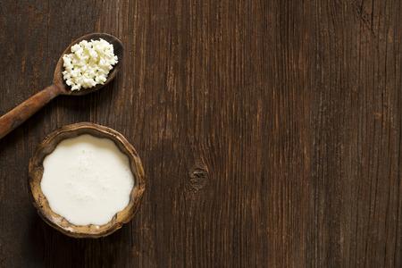 Granos de kéfir de leche en una sobrecarga de rodaje cuchara de madera Foto de archivo - 32277956