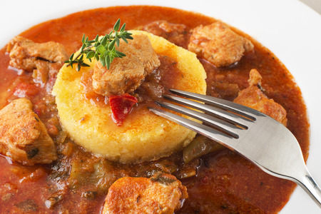 polenta: Portion of traditional meat stew - goulash on white plate Stock Photo